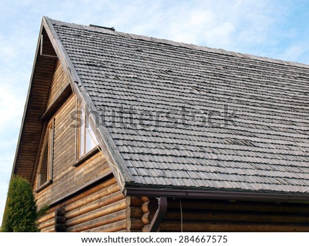 Part of house with weathered wood shingle roof - stock photo