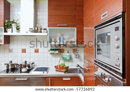 Part of Kitchen interior with wooden furniture and build in microwave oven - stock photo