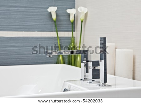 Part of modern bathroom in blue and gray tones with flowers - stock photo