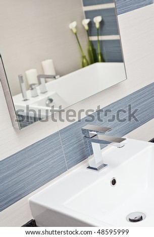 Part of modern bathroom in blue and gray tones with sink - stock photo
