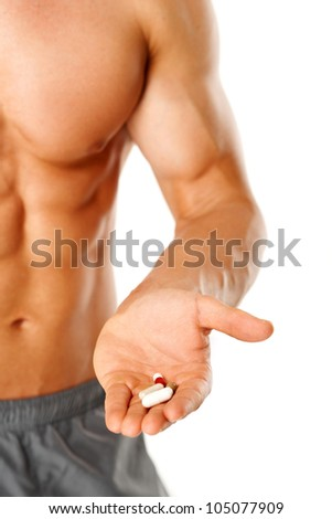 Part of muscular man torso with hand full of pills on white