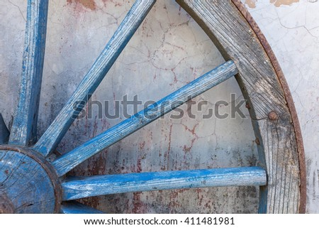 Part of old ironed, blue wagon or carriage wheel on old wall with peeling paint - stock photo