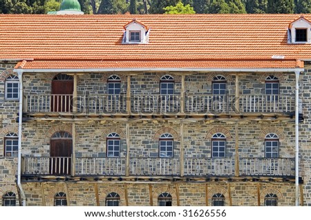 Part of old stone building with doors, windows, balconies and a tile roof, monastery St. Panteleimonos, Athos, Greece