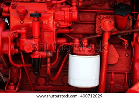 Part of old tractor engine painted in red color - stock photo