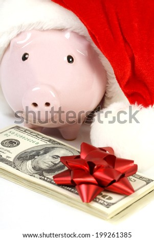 Part of piggy bank with Santa Claus hat and stack of money american hundred dollar bills with red bow standing  on white background