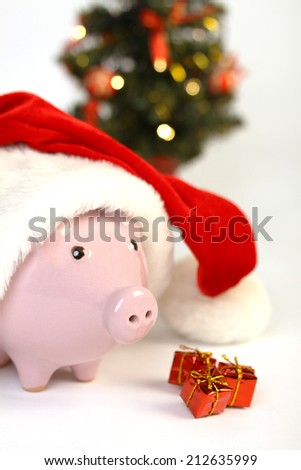 Part of piggy bank with Santa Claus hat and three little gifts and  shining christmas tree standing on white background