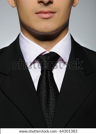 part of Portrait of succesful  business man in formal suit and black tie. gray background - stock photo