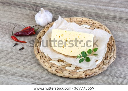 Part of round cheese on the wood background with herbs