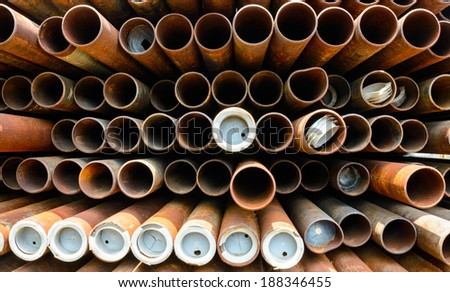 Part of rusty old pipes stacked up with natural light - stock photo