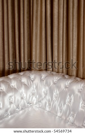 Part of silver sofa against vertical brown textured curtains with folds