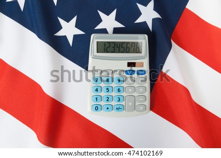 Part of studio shoot ruffled national flag with calculator over it series - United States