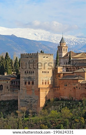 Part of the Alhambra palaces and fortifications including the Comares Tower against the Sierra Nevada mountains of Granada, Spain vertical - stock photo