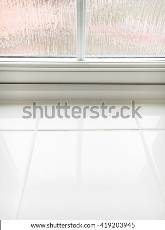 Part of the base of a double glazed window and a tiled ledge