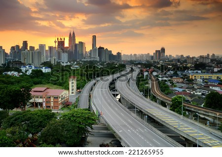 Part of the city of Kuala Lumpur and the Petronas Twin Towers or Kuala Lumpur City Centre (KLCC ) as part of the skyline at sunset  - stock photo