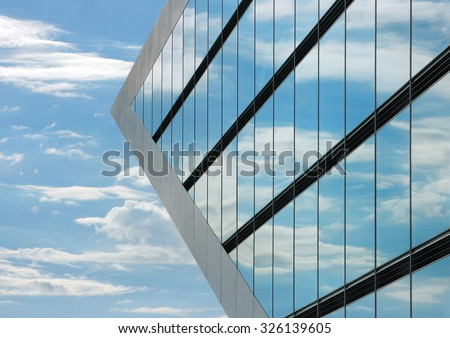 Part of the Dockland office building in Hamburg. The windows of the building reflecting the sky with clouds and creating a surreal view. - stock photo
