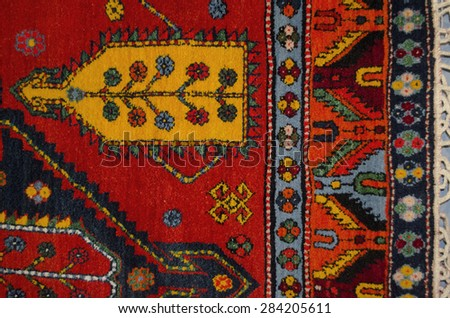 Part of the edge red woolen carpet with ethnic geometrical pattern - stock photo