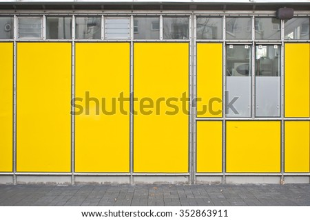 Part of the exterior of a temporary building with bright yellow panels