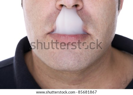 part of the face of a boy with a mouthful of smoke - stock photo