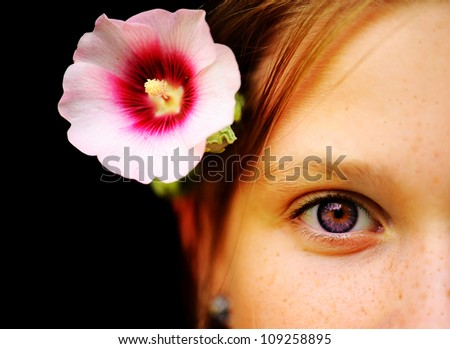 Part of the girl's face with a flower mallow - stock photo