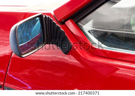 Part of the old red sports car and the car mirror