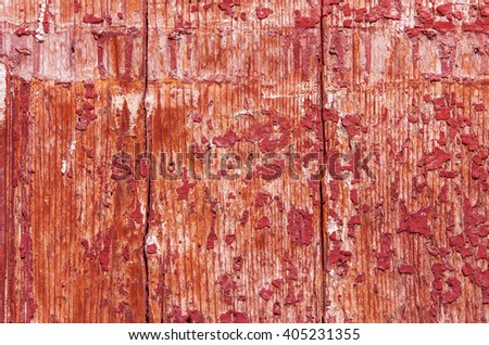 Part of the old wooden red door with paint crumbles on it. textural composition
