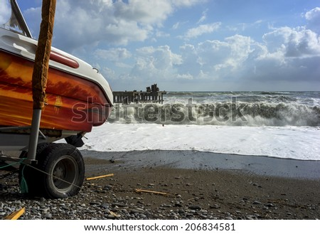 Part of the speed boat, standing on the coastline on background of big and powerful sea waves in a storm - stock photo