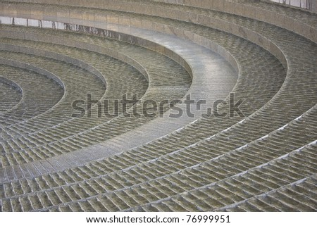 "Part of the ""Spiral Fountain"" in Darling Harbour, Sydney, Australia. Water flows over the grooved concentric steps - stock photo"