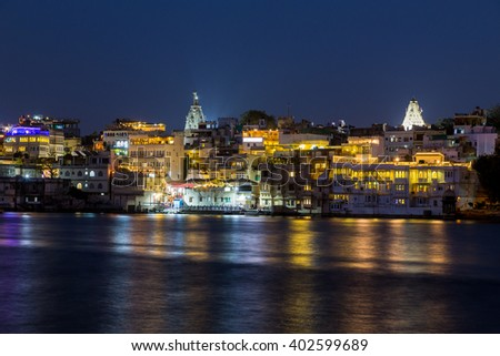 Part of the Udaipur skyline at night showing lots of buildings and reflections in Pichola lake - stock photo