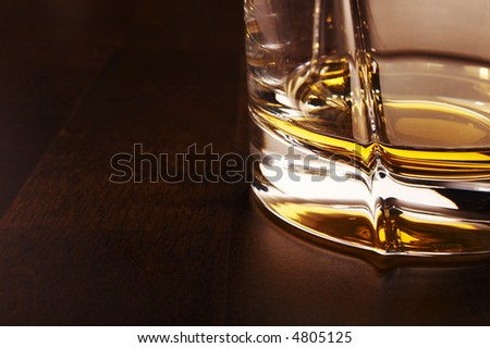 Part of the whiskey glass over a dark wooden table - stock photo