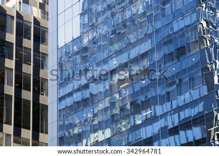 part of two different facades of high rise buildings in new york city with blue reflections in windows - stock photo