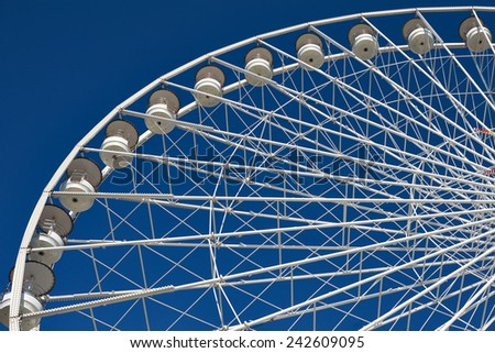Part of very large ferris wheel against blue sky - stock photo