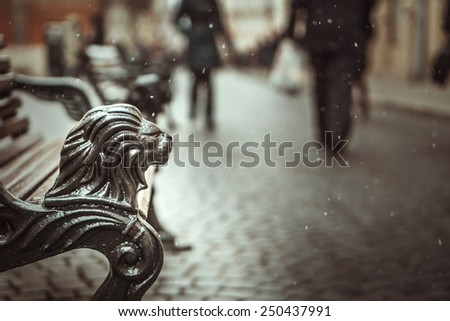 Part of vintage bench on the street with people silhouettes on background - stock photo