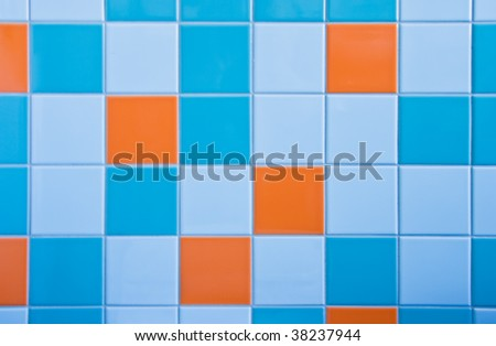 Part of wall in bathroom with tiles in light blue, azure blue and orange - stock photo