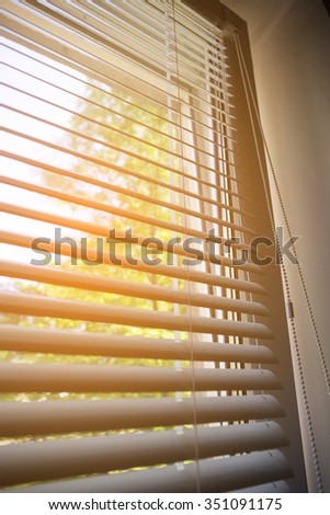 Part of window blink, nature outside behind white open jalousie - stock photo