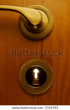 part of wooden door with metallic keyhole - stock photo
