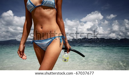 Part of young woman's body with wet skin and with a mask in hand after snorkeling in clear sea - stock photo