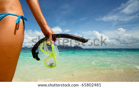 Part of young woman's body with wet skin and with a mask in hand after snorkelling in clear sea - stock photo