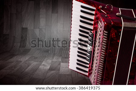 Part red accordion on wooden grey background. Write text.