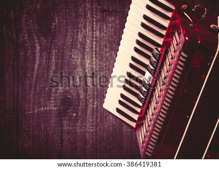 Part red accordion on wooden grey background. Write text. Vintage. - stock photo