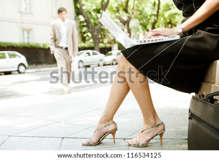 Part section of a young businesswoman working on her laptop computer while sitting in a classic street in the city with another businessman walking by. - stock photo