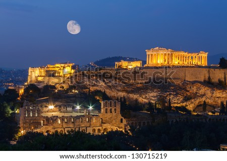Parthenon and Herodium construction in Acropolis Hill in Athens, Greece shot in blue hour with moon in the sky - stock photo