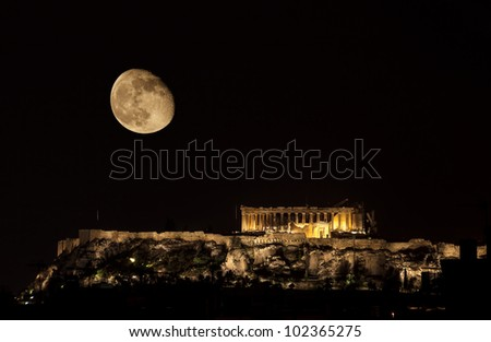 Parthenon on Acropolis Hill of Athens by night with almost full moon - stock photo