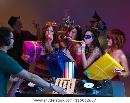 partial backview of a dj mixing, with girls blowing party horns and holding presents, at a party, with people dancing in the background - stock photo