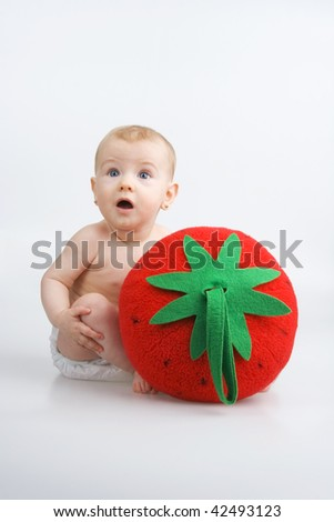 Partial child with plushy strawberry,on white background. - stock photo