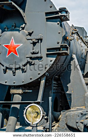 Partial frontal view of a steam locomotive. Gray metal boiler and electrical headlight - stock photo