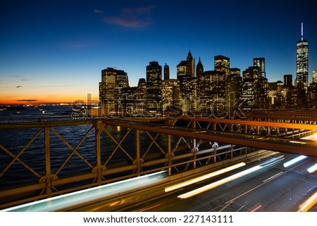 Partial New York skyline at sunset from the Brooklyn Bridge. - stock photo