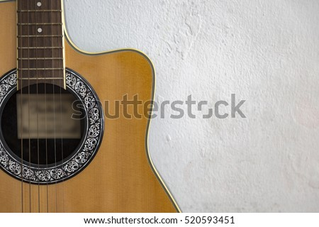 Partial of acoustic guitar isolated on concrete wall background