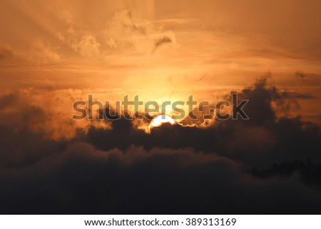 Partial of sun appears from dark cloud in the morning with golden sky - stock photo