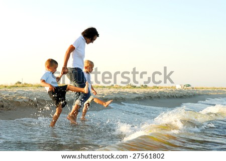 Partial profile of a woman holding the hands of two young boys, as they splash their feet in shallow water ahead of oncoming waves. - stock photo