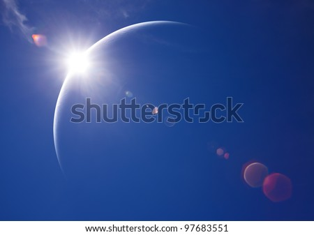 Partial Solar Eclipse with blue sky and lens flare - stock photo